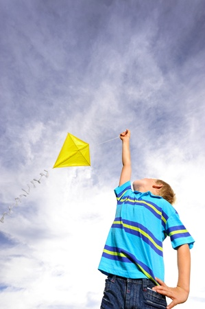 Young boy flies a yellow kite on a windy summer day