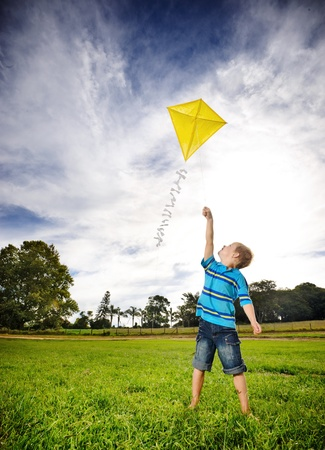 pictorial: Young boy flies his kite in an open field. a pictorial analogy for aspirations and aiming high  Stock Photo
