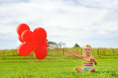 Young caucasian girl sits on grass holding a bunch of helium filled red balloons  photo