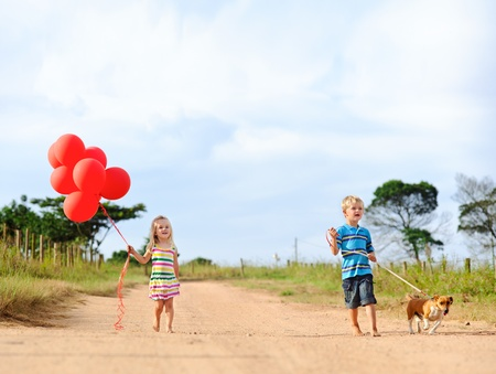 two young children walk their pet dog outdoors  Stock Photo - 9967822