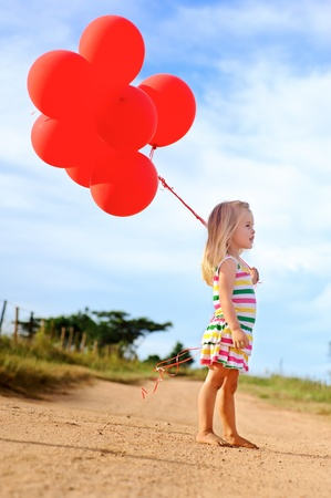 girl in red dress: Young caucasian girl walks along a path, holding a bunch of helium filled red balloons