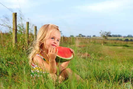 Cute blonde girl eats a watermelon in a field  Stock Photo - 9967789
