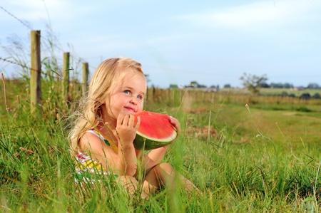 Cute blonde girl eats a watermelon in a field  Stock Photo - 9967789