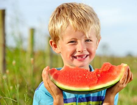 Junge, blonde Junge hält eine halbe Wassermelone gegessen; Konzept zur Förderung gesunder Ernährung