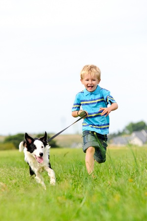 dog running: Young boy runs in a green field with his pet collie