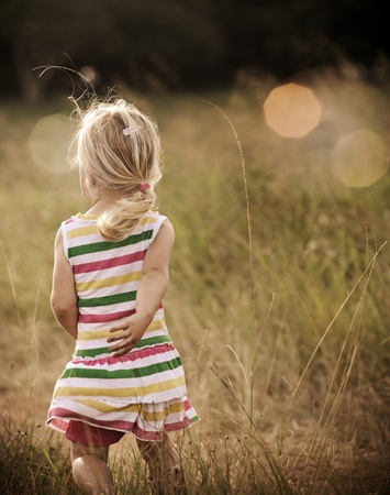 Back view of a young blond girl running happily in an open field, graded with a vintage tone  photo