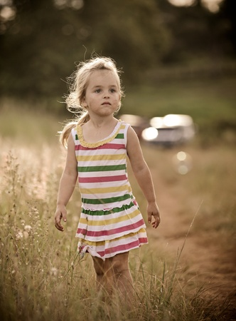 Cute blond girl walks within tall grass in a field  Stock Photo - 9967785
