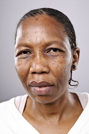 Old African woman looks at camera with sad eyes photo