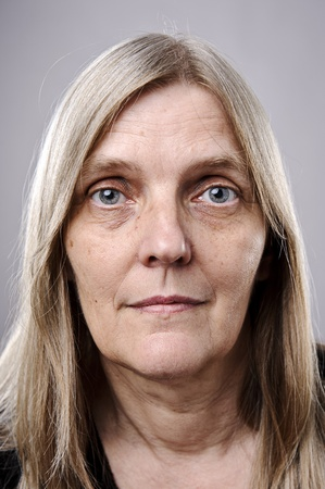 women face stare: wrinkled blonde woman poses for a portrait in studio