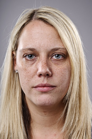 Freckle faced girl poses for a high detail closeup portrait photo