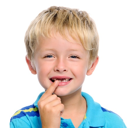 Young blond child points to his missing teeth photo