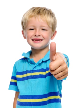 affirm: Happy young boy has his thumbs up; selective focus on hand