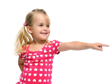 kid friendly: cute blonde girl with pigtails points in a direction, isolated on white in studio