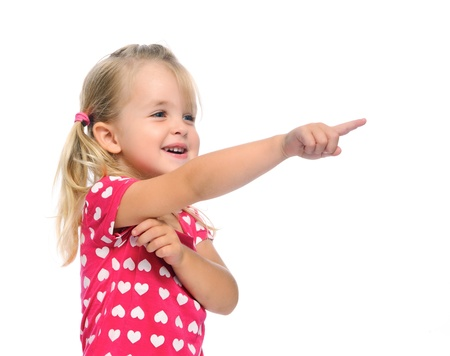 child finger: cute blonde girl with pigtails points in a direction, isolated on white in studio