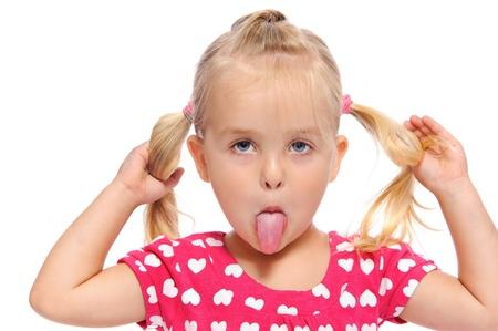 sacar la lengua: Funny little girl hace una cara tonta mientras tira sobre sus coletas