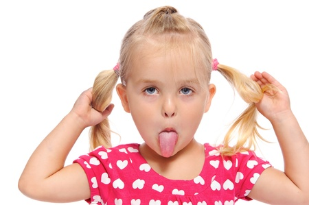 pulling faces: funny little girl makes a silly face while pulling on her pigtails