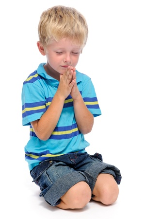 Young blonde child clasps his palms together in prayer, isolated on white  photo