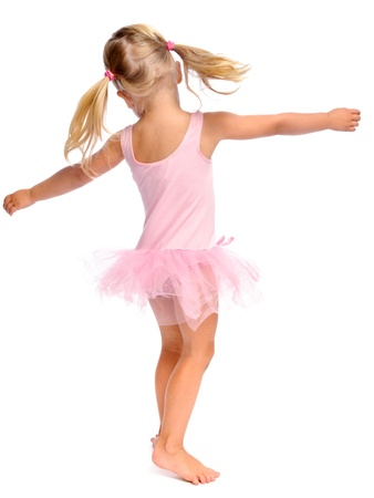 young girl dances ballet in her ballerina tutu, isolated on white in studio  photo