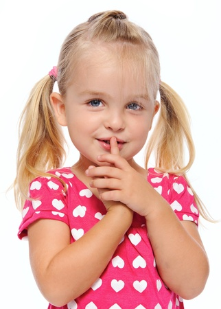 little finger: young girl with finger on lips gestures to be quiet  Stock Photo