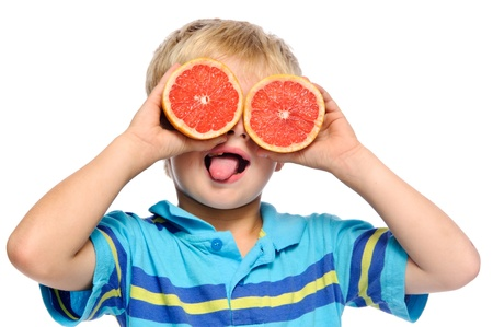 cheeky: Blond boy covers eyes with ruby grapefruit and sticks his tongue out