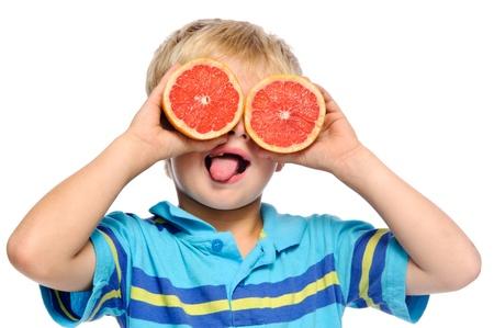 lengua afuera: Ni�o rubio cubre los ojos con pomelo Rub� y sobresale su lengua  Foto de archivo