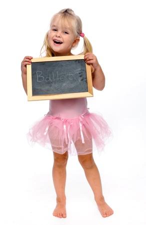 ballet studio: young ballerina smiling in studio holding ballet sign  Stock Photo