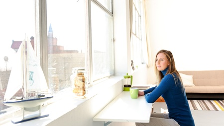 Woman has coffee in her loft apartment overlooking the city photo