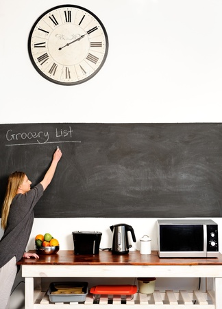 pantry: Young blond woman stretches out to write on a blackboard in the kitchen