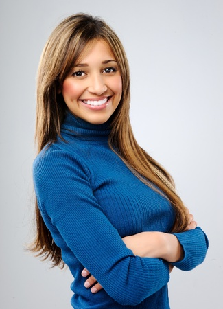 Friendly mixed race model smiles in studio, isolated on grey Stock Photo - 10737413