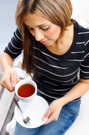 Young attractive woman drinking a cup of tea, top down perspective Stock Photo - 10737403