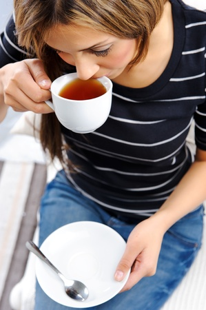 Young attractive woman drinking a cup of tea, top down perspective Stock Photo - 10737375