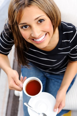 Young attractive woman is happy with her cup of tea, top down perspective Stock Photo - 10737389