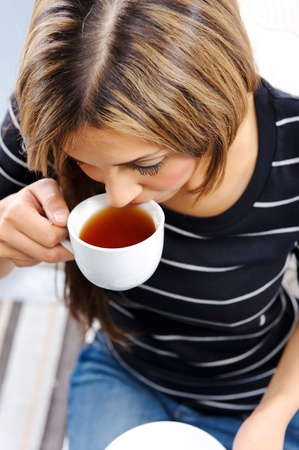 Young attractive woman drinking a cup of tea, top down perspective Stock Photo - 10737402