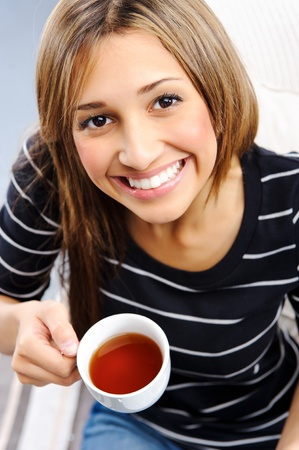 Young attractive woman is happy with her cup of tea, top down perspective Stock Photo - 10737398