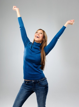woman mouth open: Attractive brunette raises her arms in the air in triumphant, after hearing of her success