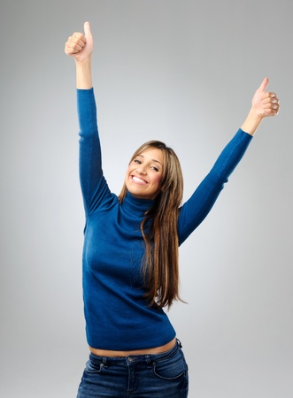 triumphant: Attractive brunette raises her arms in the air in triumphant, after hearing of her success