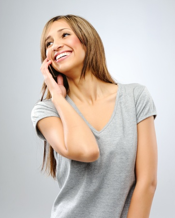 sideways glance: Happy smiling brunette looks sideways while on the phone