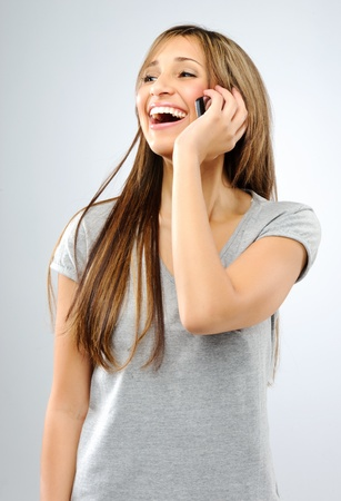Beautiful young woman laughs while talking on her cellphone, in studio  photo
