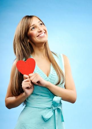 profesar: Joven y bella mujer mira hacia arriba y tiene un coraz�n rojo de profesar su amor