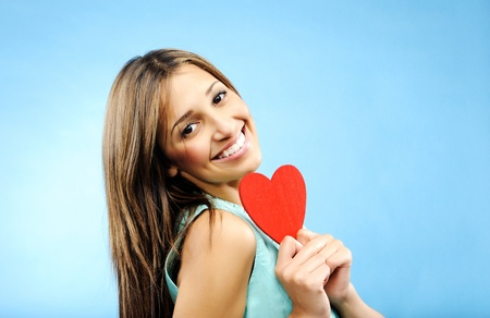 profess: Happy, smiling young woman holds out a red heart to profess her love  Stock Photo
