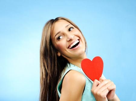 profesar: Hermosas sonrisas joven mujer sobre su hombro y mantiene un coraz�n rojo de profesar su amor Foto de archivo