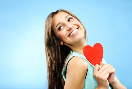 profess: Beautiful young woman smiles over her shoulder and holds out a red heart to profess her love  Stock Photo