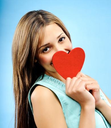profesar: Hermosa mujer joven se esconde detr�s de un coraz�n rojo t�mido para profesar su amor Foto de archivo