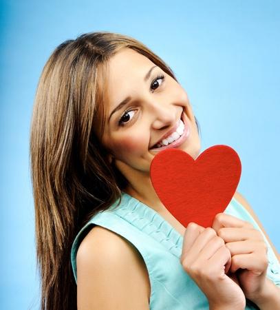 profesar: Mujer feliz, sonriente joven sostiene un coraz�n rojo de profesar su amor Foto de archivo