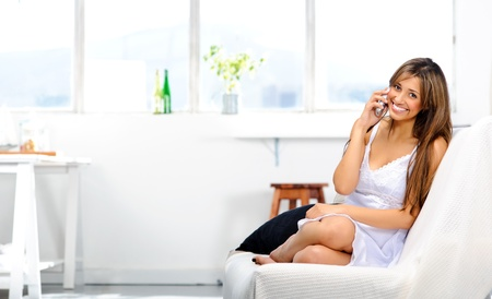 Attractive young mixed race woman relaxing on the couch, catching up with her friend on the telephone Stock Photo - 10737244