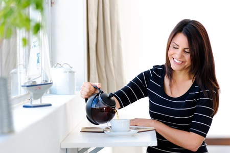 Happy woman tops up her tea while reading her book Stock Photo - 10803067