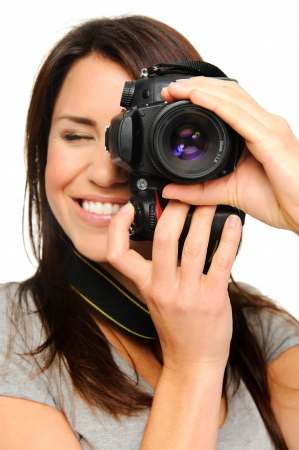 slr cameras: Attractive brunette aims her camera. composing a photograph in studio, isolated on white Stock Photo