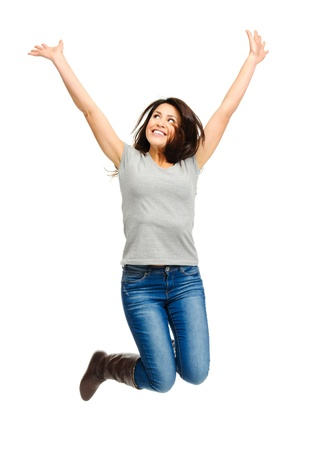 triumphant: Pretty woman celebrates by jumping and cheering in studio, isolated on white  Stock Photo