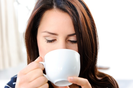 Pretty brunette drinking a hot beverage  Stock Photo - 10803049