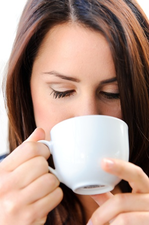 smells: Pretty girl smells her morning coffee  Stock Photo